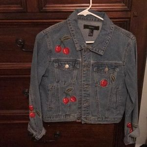Denim jacket embroidered with cherries.